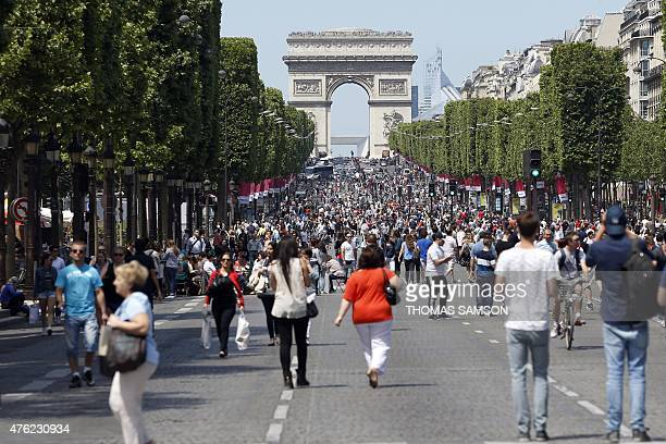 People walk on the Champs Elysees made pedestrian for the day and where a food and fresh products marketplace stands on June 7 2013 in Paris AFP...