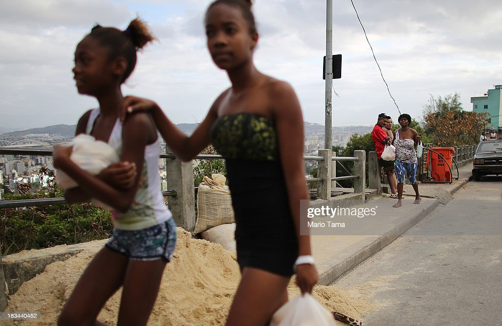 People walk on the day of a 'pacification' operation in the favela complex of Lins de Vasconcelos, in the North Zone, on October 6, 2013 in Rio de Janeiro, Brazil. The favela complex, or shanty town, was previously controlled by drug traffickers and will now be occupied by the city's 35th UPP or 'Police Pacification Unit'. The favela pacifications are occurring amid Rio de Janeiro's efforts to improve security ahead of the 2014 FIFA World Cup and 2016 Olympic Games.