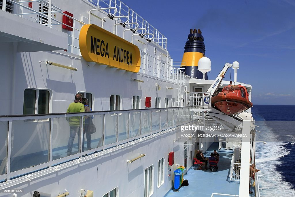 People walk on the deck of the new ferry boat Mega Andrea of the French Corsica Ferries company on May 31, 2016, between in Porto-Vecchio on the French Mediterranean island of Corsica and Golfo Aranci on the Italian Mediterranean island of Sardegna. The Corsica Ferries opened, on May 31, a new line between Nice, Corsica and the island of Sardegna in Italy, reinforcing its position as a leader for the maritime transport between the two neighbour islands Corsica and Sardegna. / AFP / PASCAL