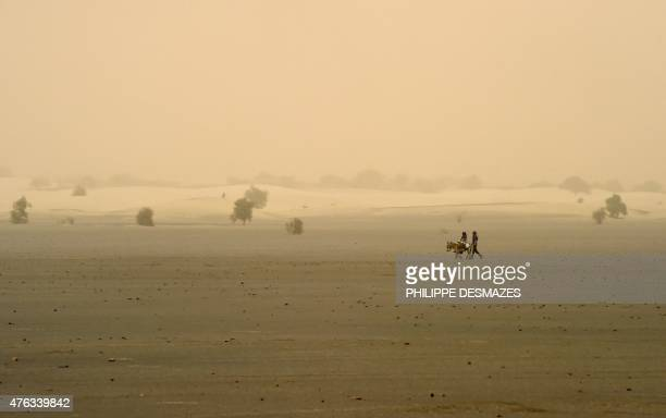 People walk on the dry lake of Faguibine near Bintagoungou in the region of Timbuktu northern Mali on June 4 while French soldiers of the 93rd French...