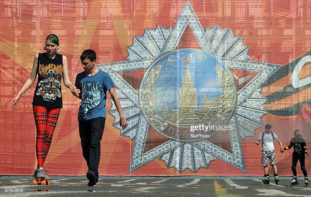 People walk on the Dvortsovaya Square with a huge poster in the background dedicated to Victory Day in St. Petersburg, Russia, on May, 3, 2016. On 09 May, Russia will celebrate the 71st anniversary of the victory of the Soviet Union and its Allies over Nazi Germany in WWII