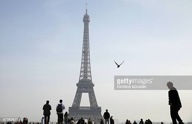 People walk on the esplanade du Trocadero near the Eiffel tower in central Paris on March 11 2014 AFP PHOTO / PATRICK KOVARIK