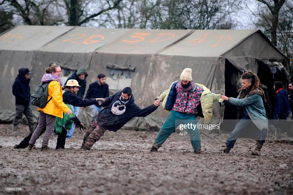 People walk on the mud during a music festival organized by opponents against a project of international airport on January 5, 2013 in Notre-Dame-des-Landes, western France. The project was signed in 2010 and the international airport is supposed to open in 2017 near the city of Nantes. AFP PHOTO JEAN-SEBASTIEN EVRARD