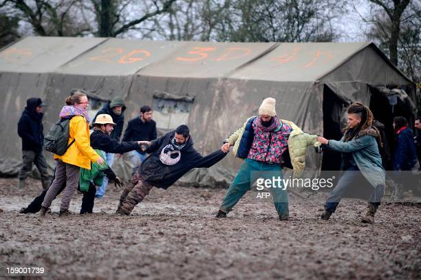 People walk on the mud during a music festival organized by opponents against a project of international airport on January 5 2013 in...