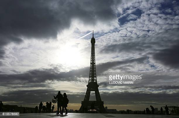 People walk on the parvis des droits de l'homme square in front of the Eiffel tower on October 19 2016 in Paris moments after sunrise / AFP / LUDOVIC...