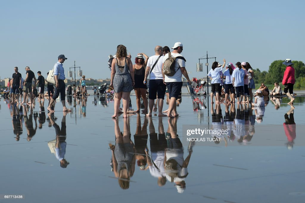 People walk on the pavement of the water mirror fountain, whose system alternates a mirror effect with a mist effect, on June 19, 2017 in Bordeaux's city center, southwestern France. French national meteorological service, Meteo France has placed 16 departments on orange alert for heatwaves, with temperatures between 33°C et 38°C expected in the Paris region and southwestern France. /