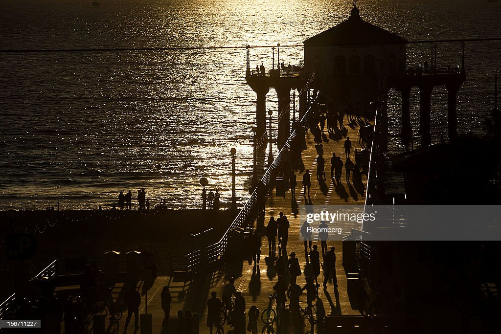 People walk on the pier at sunset in Manhattan Beach, California, U.S., on Sunday, Nov. 11, 2012. California faces a $1.9 billion spending gap through the end of the next fiscal year as revenue is projected to fall short of forecasts and spending exceeds estimates, the state's independent fiscal analyst said. Photographer: Patrick Fallon/Bloomberg via Getty Images