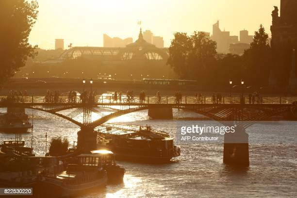 TOPSHOT People walk on the Pont des Arts pedestrian bridge in Paris on July 25 2017 / AFP PHOTO / ludovic MARIN