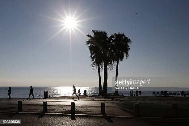 People walk on the 'Promenade des Anglais' on the French Riviera city of Nice southeastern France on December 27 2015 / AFP / VALERY HACHE