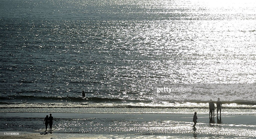 People walk on the shoreline Brandenburger Beach on July 21, 2013 in Westerland, Germany. The weather forecast for the next three days predicts sunny weather with heights of 30 Celsius for the north of Germany.