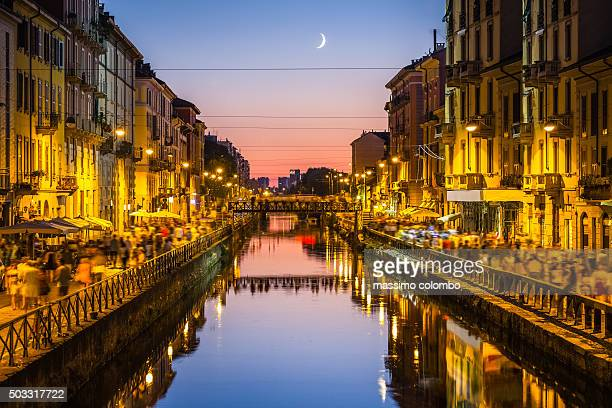 People walk on the sides of the Naviglio Grande canal in Milan