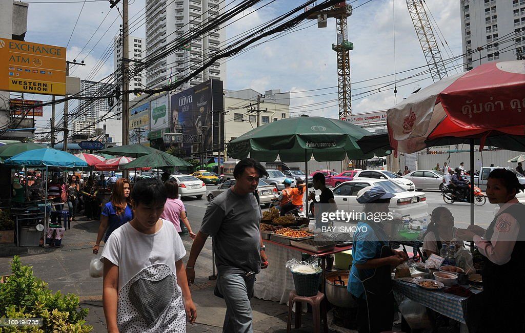 People walk on the sidewalk of a busy road in downtown Bangkok on May 25, 2010. Thailand's economy grew at breakneck pace early this year but the deadly unrest that began in March will clip the full-year performance by 1.5 percentage points, officials said. AFP PHOTO / Bay ISMOYO