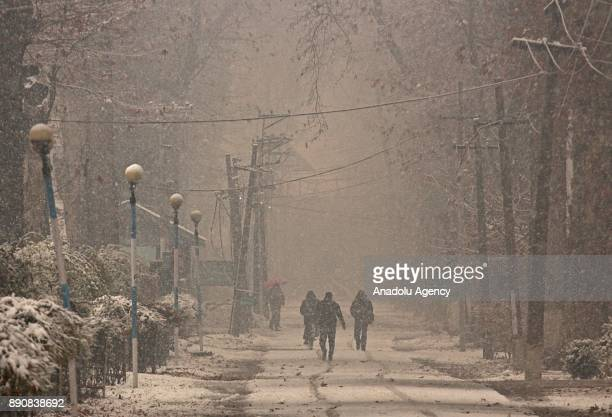 People walk on the snow covered road as it snows in Srinagar the summer capital of Indian controlled Kashmir on December 12 2017 Heavy snowfall...