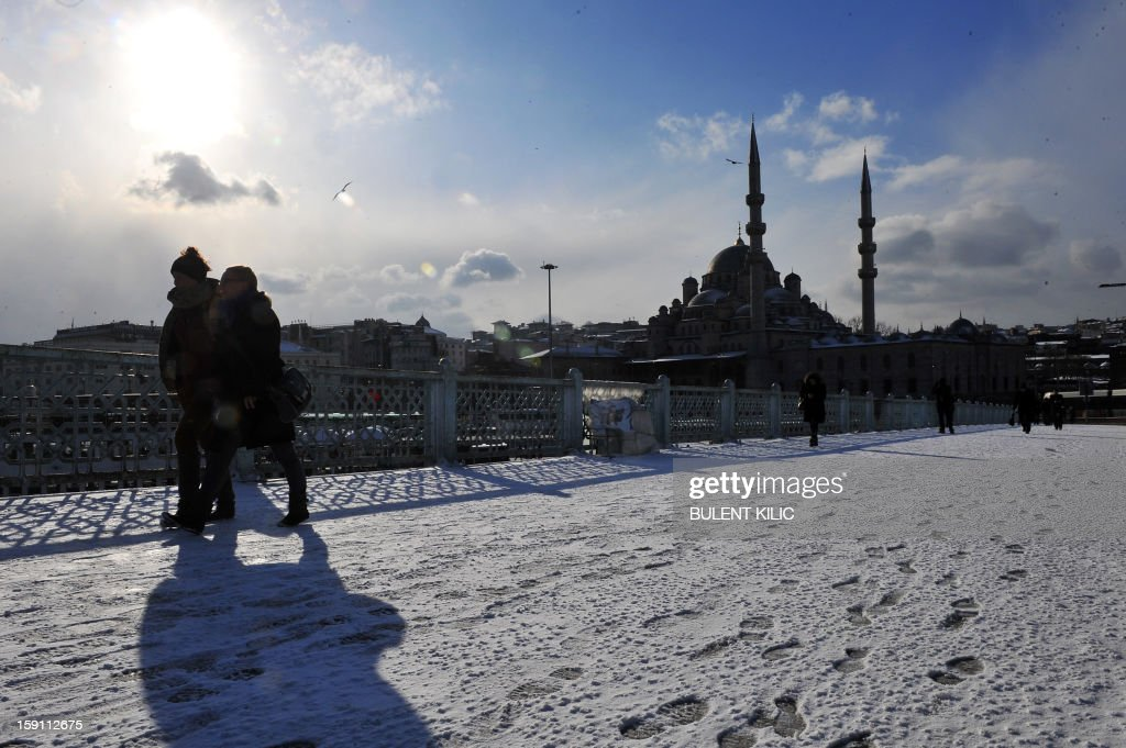 People walk on the snow-covered Galata Bridge in Istanbul on January 8, 2013. Heavy snowfall blanketed Turkey's commercial hub Istanbul, a city of 15 million, paralysing daily life, disrupting air traffic and land transport. Officials said the snow is expected to continue until late tomorrow, according to the weather forecast.