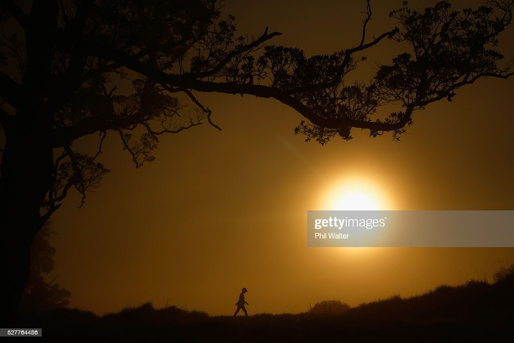 People walk on the summit of Mt Eden as the sun struggles to shine through a blanket of fog over Auckland City on May 4, 2016 in Auckland, New Zealand. The morning fog disrupted flights and ferry services in the city.