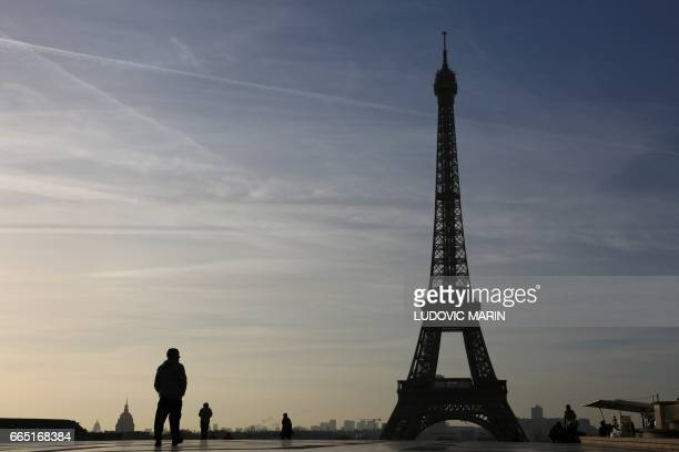 People walk on the trocadero plaza at sunrise in front of the Eiffel tower on April 6 in Paris / AFP PHOTO / LUDOVIC MARIN