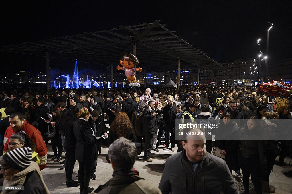 People walk on the Vieux-Port harbour as they attend on January 12, 2013 in the French southern city of Marseille, the light parade, part of the launching of Marseille-Provence 2013 European Capital of Culture. The event marks the start of a year, leading to a cultural renaissance in France's second-largest metropolitan area.
