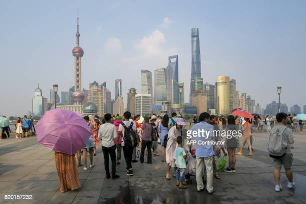 People walk on the waterfront bund in Shanghai on July 21 2017 Shanghai sweltered under a new record high of 409 degrees Centigrade on July 21...