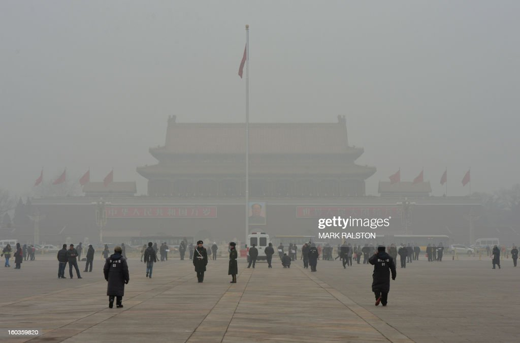 People walk on Tiananmen Square in front of Tiananmen Gate with the portrait of Mao Zedong (C) during heavy air pollution in Beijing on January 30, 2013. Beijing urged residents to stay indoors on January 30 as emergency measures were rolled out aimed at countering a heavy cloud of smog blanketing the Chinese capital and swathes of the country. AFP PHOTO/Mark RALSTON