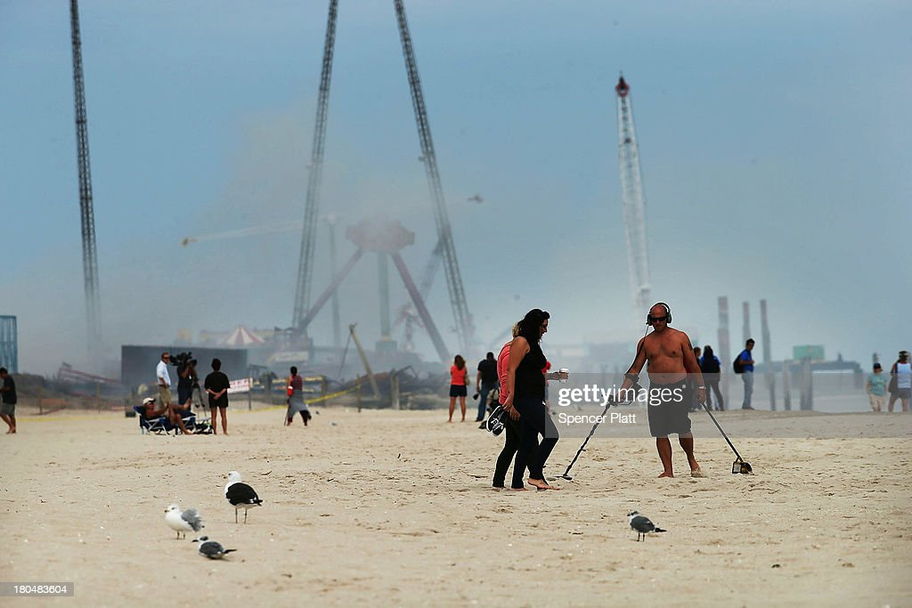 People walk onthe beach near the scene of a massive fire that destroyed dozens of businesses along an iconic Jersey shore boardwalk on September 13, 2013 in Seaside Heights, New Jersey. The 6-alarm fire began in a frozen custard stand on the recently rebuilt boardwalk around 2:00 p.m. on September 12, and quickly spread in high winds. While there were no injuries reported, many businesses that had only recently re-opened after Hurricane Sandy, were destroyed in the blaze.