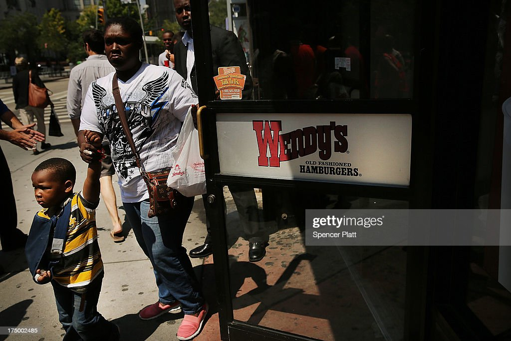 People walk out of a Wendy's restaurant as employees and supporters demonstrate outside to demand higher pay and the right to form a union on July 29, 2013 in New York City. Across the country thousands of low-wage workers are expected to walk off their jobs Monday at fast food establishments in seven U.S. cities. Workers at KFC, Wendy's, Burger King, McDonald's and other restaurants are calling for a living wage of $15 an hour and the right to form a union without retaliation.