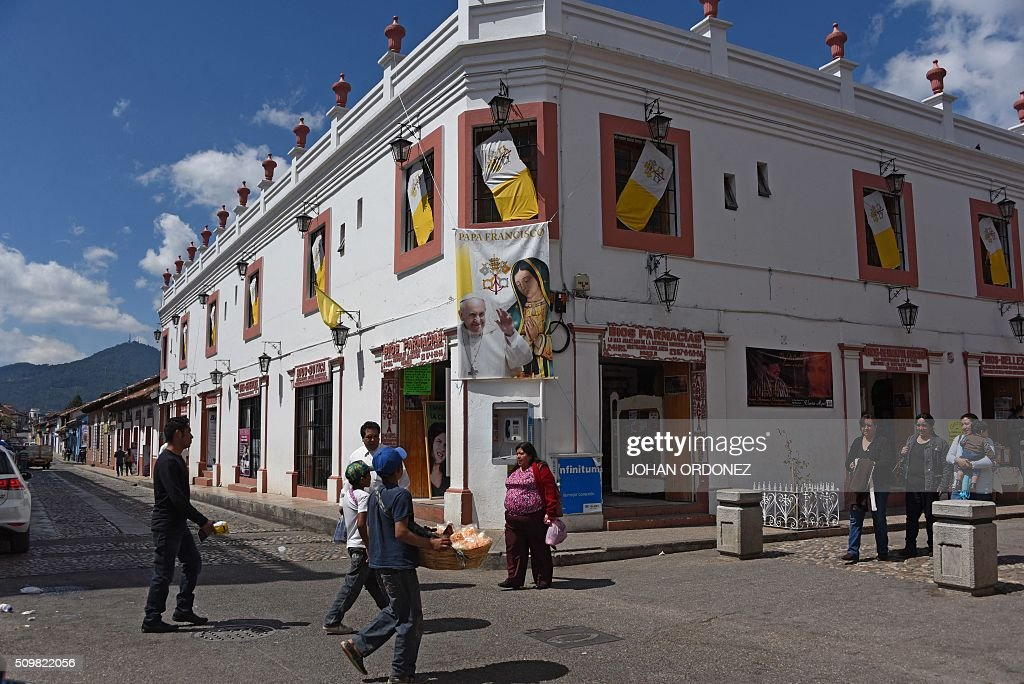 People walk outside a store with a poster of Pope Francis in San Cristobal de las Casas, Chiapas State, Mexico on February 12, 2016. Pope Francis will arrive in Mexico on Friday, where he will visit until February 17. AFP PHOTO/Johan ORDONEZ / AFP / JOHAN ORDONEZ