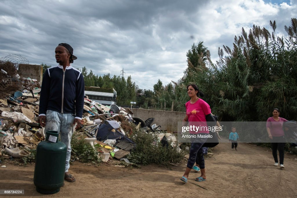 People walk outside an occupied building on October 4, 2017 in Rome, Italy.For the last 5 years, hundreds of people, including Italians, Roma and refugees, including around 35 children, have lived in an occupied building on the suburbs of Rome without electricity or a toilet and surrounded by refuse.