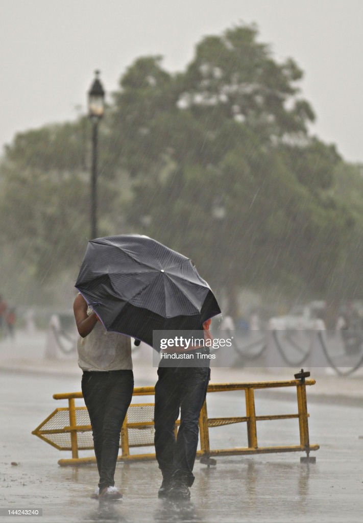People walk outside as Delhi witnesses heavy rain fall after a dust storm due to which temperature has fallen by few degrees on May 12, 2012 in New Delhi, India.