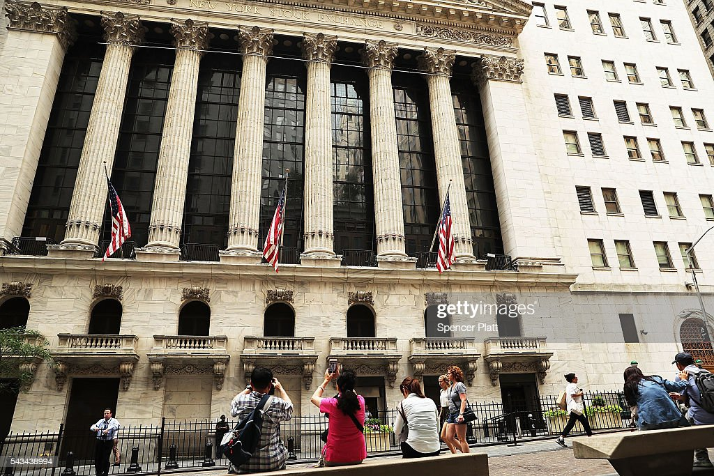 People walk outside of the New York Stock Exchange (NYSE) at the close of the trading day on June 28, 2016 in New York City. Following days of market turbulence due to Britain's vote to separate from the European Union, markets bounced back today with the Dow Jones industrial average rising over 200 points.