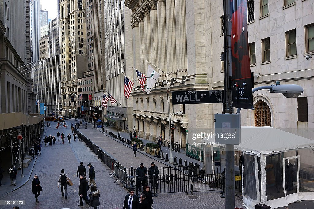 People walk outside of the New York Stock Exchange on March 5, 2013 in New York City. The Dow Jones industrial average rallied to a record high on Tuesday to close for the day at 14,253.77, beating its old 2007 record.