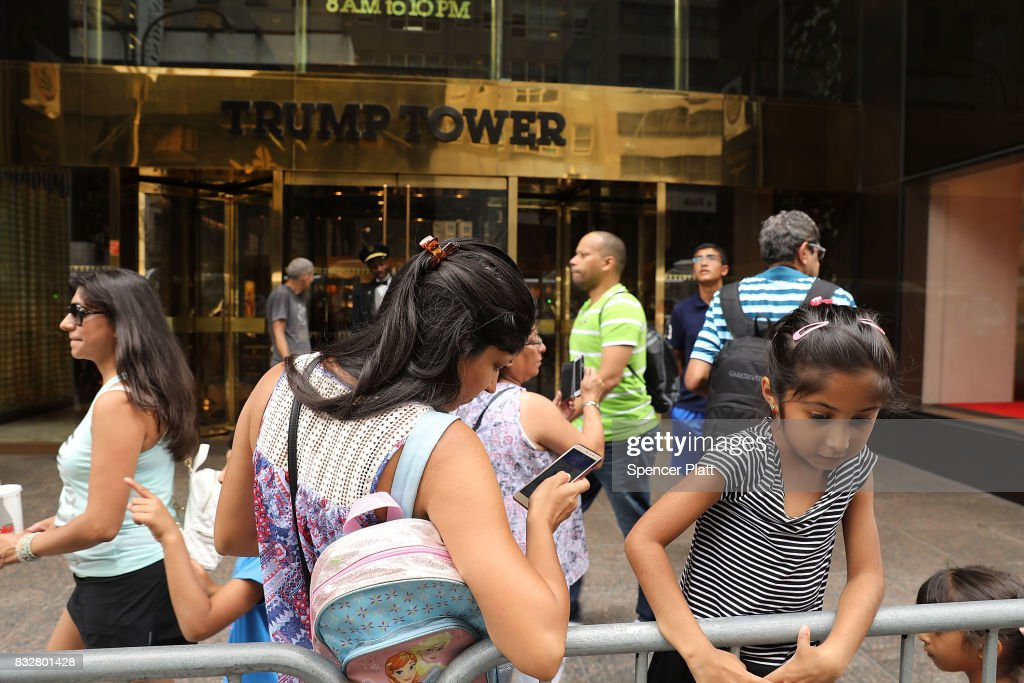 People walk outside of Trump Tower after it re-opened to the public following the departure of US President Donald Trump on August 16, 2017 in New York City. President Trump arrived at his residency at the tower on Monday evening, his first trip back to Trump Tower since the inauguration.