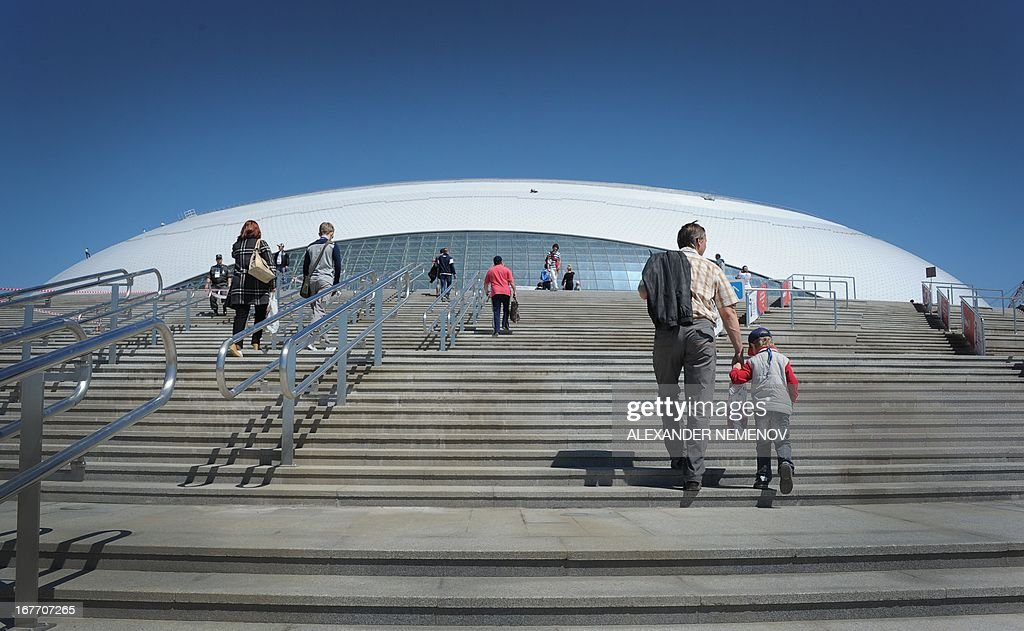People walk outside the Bolshoi Ice Dome arena - ice hockey venue at the Olympic Park in Adler outside Sochi, during the IIHF U18 International Ice Hockey World Championship on April 28, 2013.