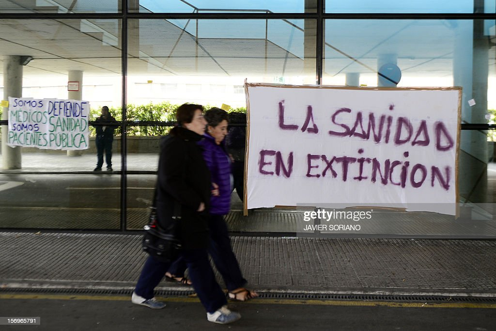 People walk outside the Hospital Clinico San Carlos in Madrid where Spanish doctors, nurses and hospital staff denounce budget cuts and privatisations on November 26, 2012. The health sector has been hard hit by the austerity policies implemented by the rightwing government of Mariano Rajoy, which is trying to cut the public deficit in the eurozone's fourth largest economy. The banner reads: 'health in extinction.'