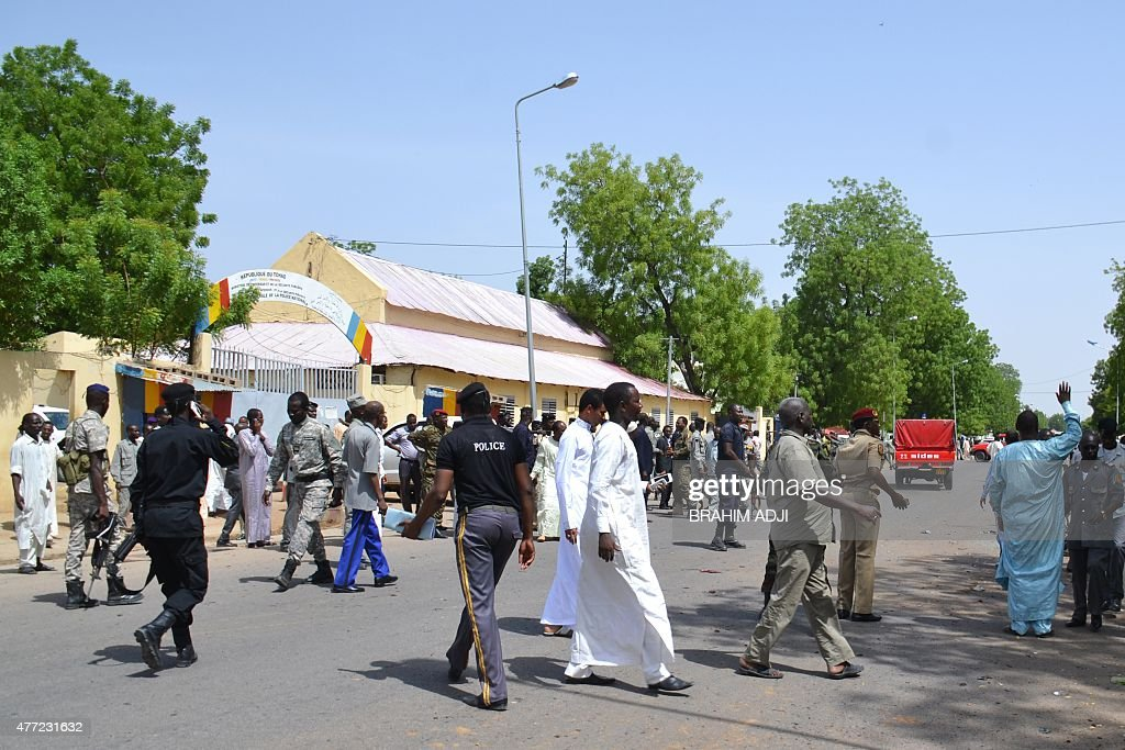 People walk outside the police headquarters in N'Djamena on June 15 2015 after a suicide bomb attack which killed 23 along with a simultaneous...