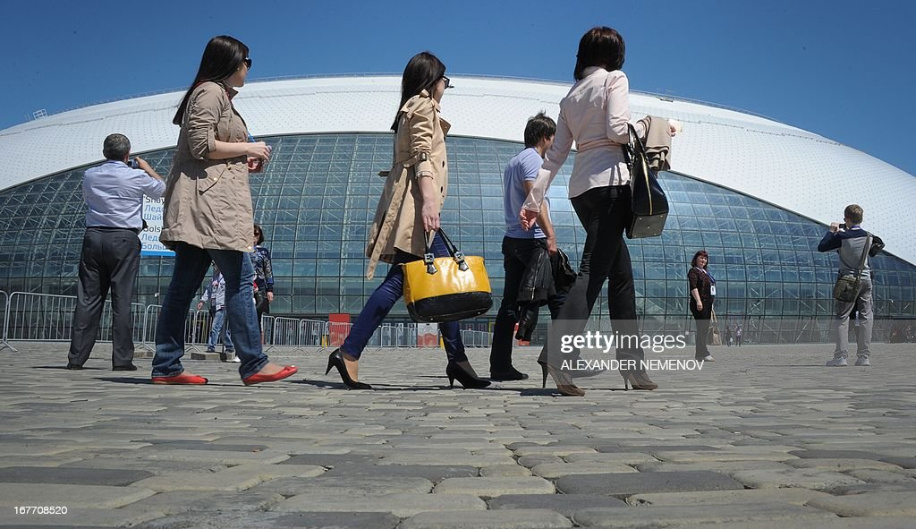 People walk outside the the Bolshoi Ice Dome arena - ice hockey venue at the Olympic Park in Adler outside Sochi, during the IIHF U18 International Ice Hockey World Championship on April 28, 2013.