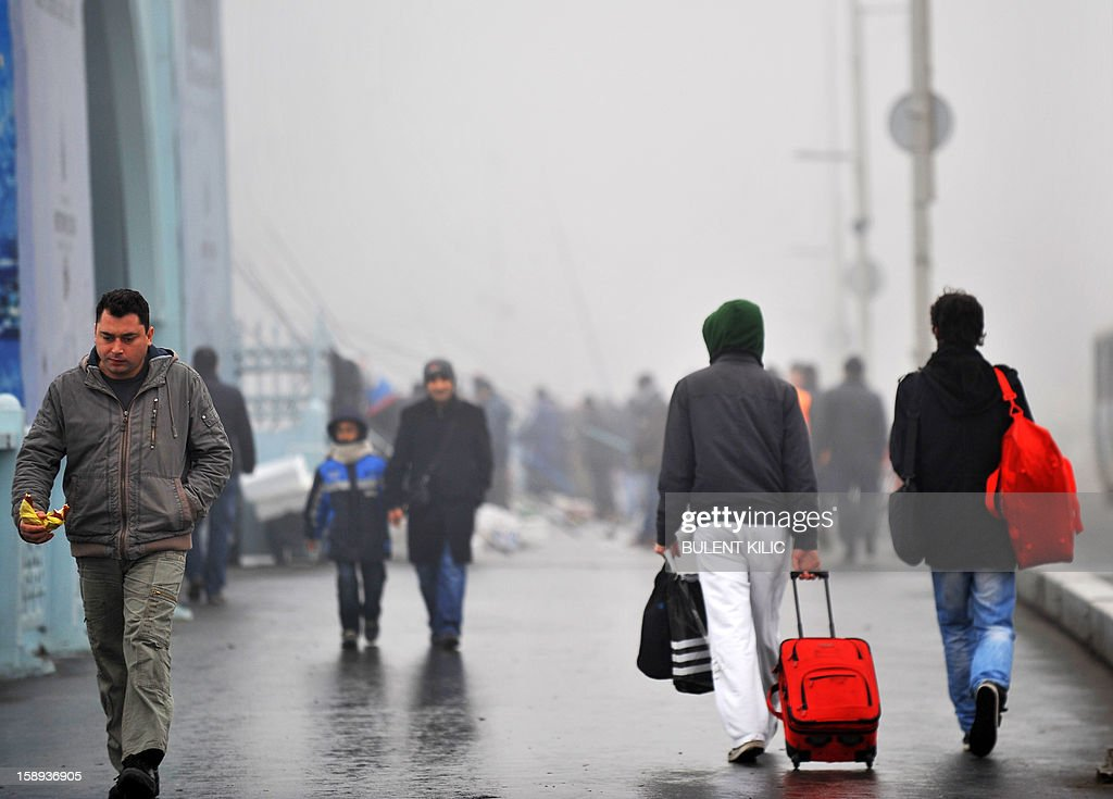 People walk over Galata bridge in heavy fog early on January 4, 2013, in Istanbul over the Bosphorus. River traffic was brought to a halt this morning due to fog conditions.
