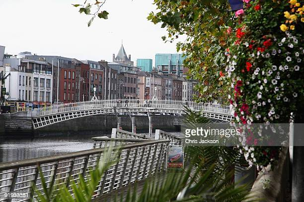 People walk over over Ha'penny Bridge on October 15 2009 in Dublin Ireland Dublin is Ireland's capital city located near the midpoint of Ireland's...