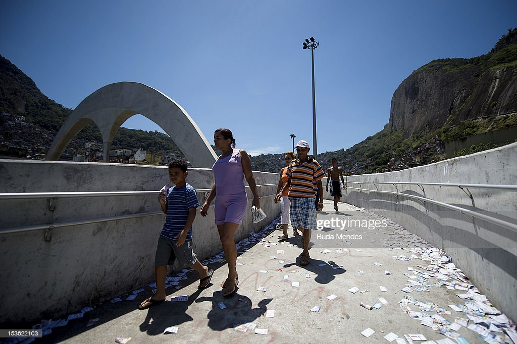 People walk over pamphlets as their head to a polling station in Rio de Janeiro's Rocinha shantytown on October 07, 2012 in Rio de Janeiro, Brazil.