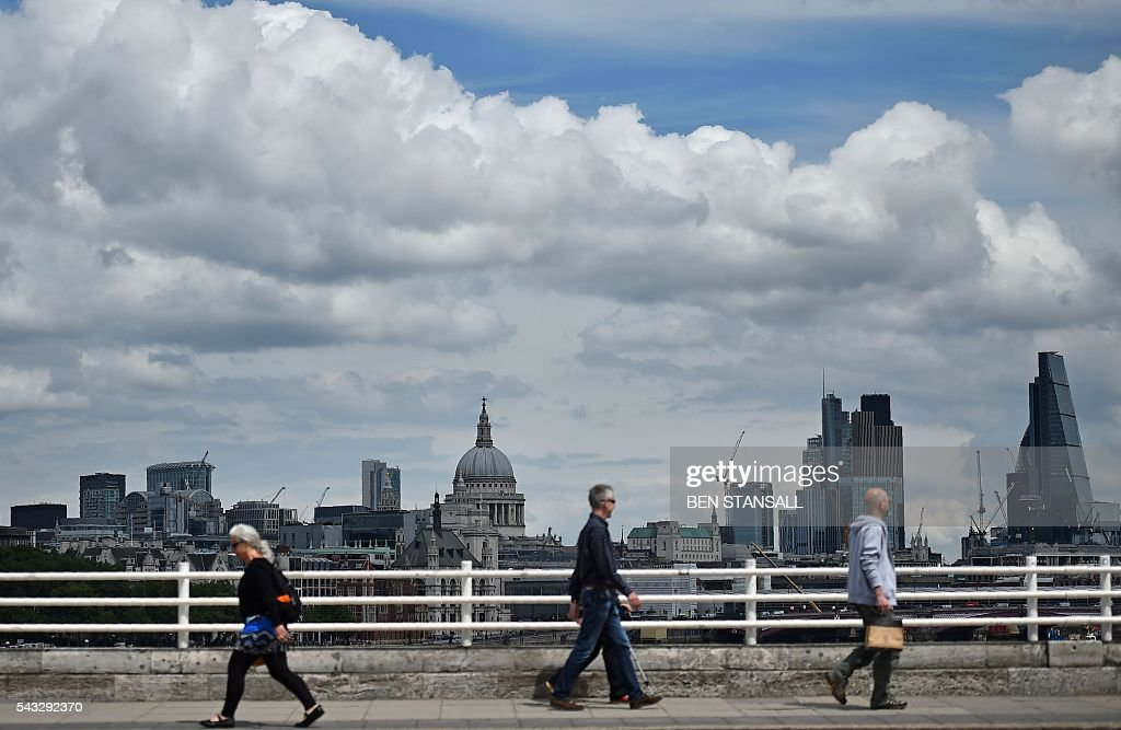 People walk over Waterloo bridge with a backdrop of St Paul's Cathedral and buildings in City of London in central London on June 27, 2016. Britain began preparations to leave the European Union on Monday but said it would not be rushed into a quick exit, as markets plunged in the wake of a seismic referendum despite attempts to calm jitters. / AFP / BEN