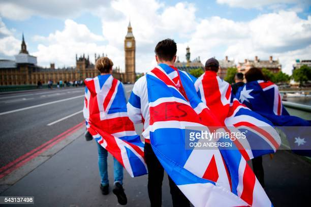 People walk over Westminster Bridge wrapped in Union flags towards the Queen Elizabeth Tower and The Houses of Parliament in central London on June...