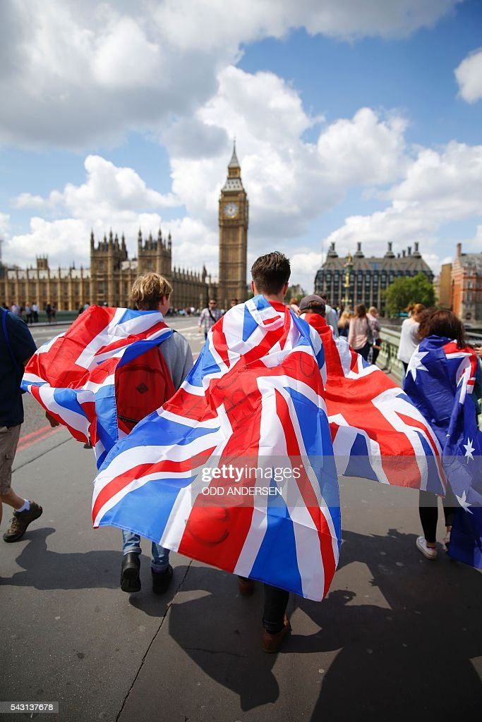 People walk over Westminster Bridge wrapped in Union flags, towards the Queen Elizabeth Tower (Big Ben) and The Houses of Parliament in central London on June 26, 2016. Britain's opposition Labour party plunged into turmoil Sunday and the prospect of Scottish independence drew closer, ahead of a showdown with EU leaders over the country's seismic vote to leave the bloc. Two days after Prime Minister David Cameron resigned over his failure to keep Britain in the European Union, Labour leader Jeremy Corbyn faced a revolt by his lawmakers who called for him, too, to quit. / AFP / Odd ANDERSEN