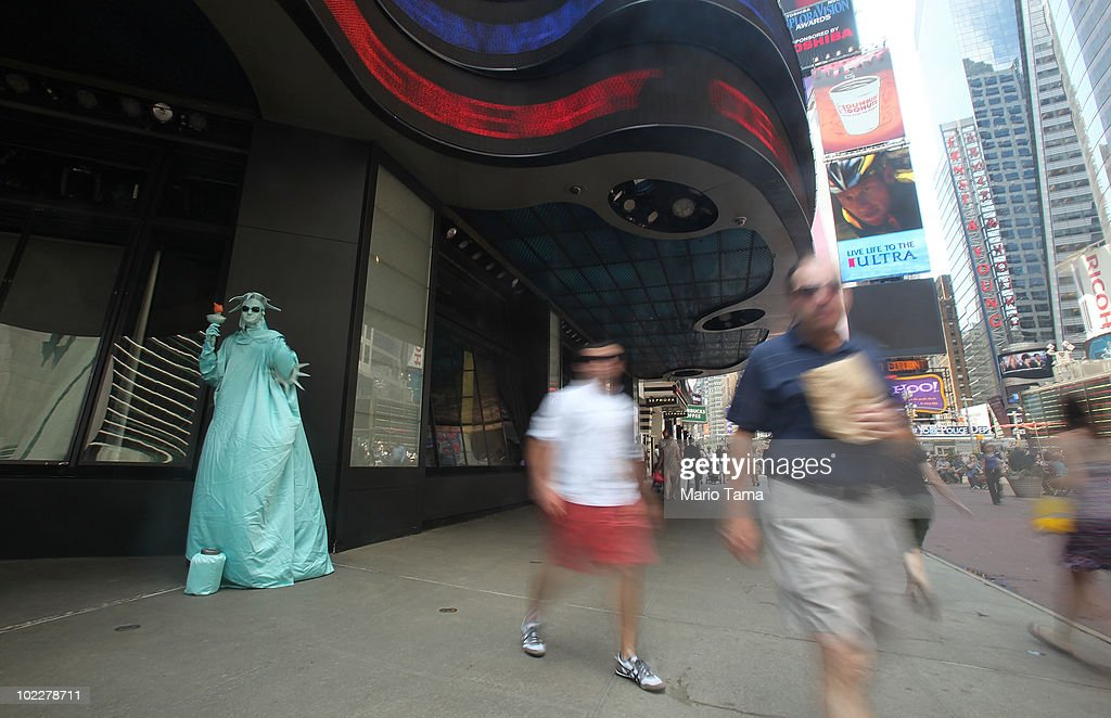 People walk pass a person dressed as the Statue of Liberty in Times Square on June 21, 2010 in New York City. Accused Times Square bomber Faisal Shahzad is slated to be arraigned this afternoon on ten counts of terror and weapons charges.