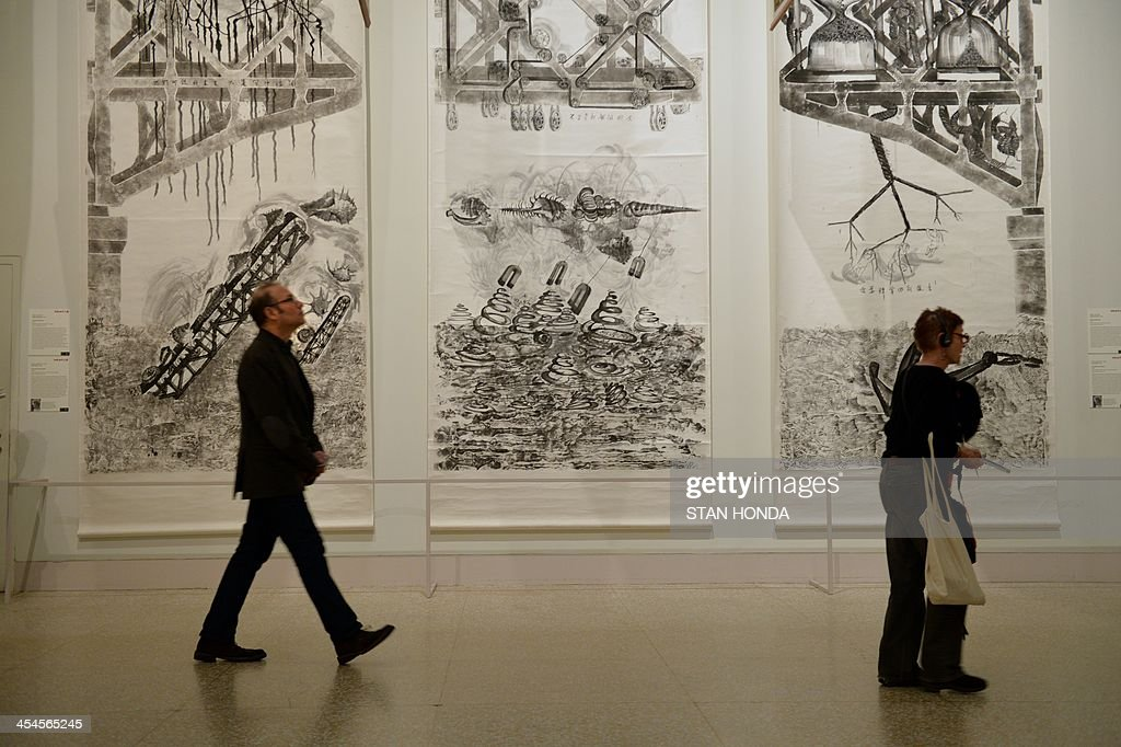 People walk past '30 Letters to Qiu Jiawa', three hanging scrolls by Qiu Zhijie in the exhibition 'Ink Art: Past as Present in Contemporary China' at the Metropolitan Museum of Art on December 9, 2013 in New York. A major exhibition of 70 pieces of art by 35 contemporary artists born in China goes on view to the public on December 11. AFP PHOTO/Stan HONDA ++RESTRICTED