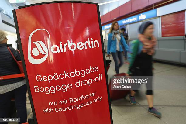 People walk past a baggage dropoff counter of German airliner Air Berlin at Tegel Airport on September 26 2016 in Berlin Germany According to media...