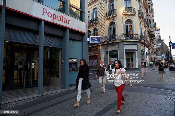 People walk past a Banco Popular branch on September 21 2016 in Madrid Spain Spain's Banco Popular plans to cut around 3000 jobs and close 300...