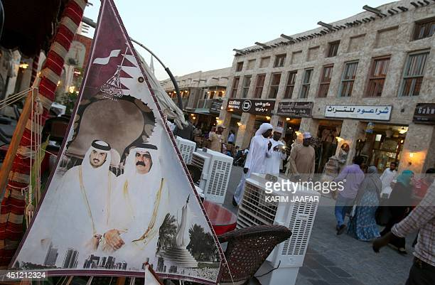 People walk past a banner bearing portraits of former emir of Qatar Sheikh Hamad bin Khalifa alThani and his son Sheikh Tamim who acceded to the...
