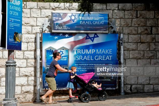 People walk past a banner in support of US President Donald Trump on the day of his visit in Jerusalem on May 22 2017 / AFP PHOTO / Menahem KAHANA