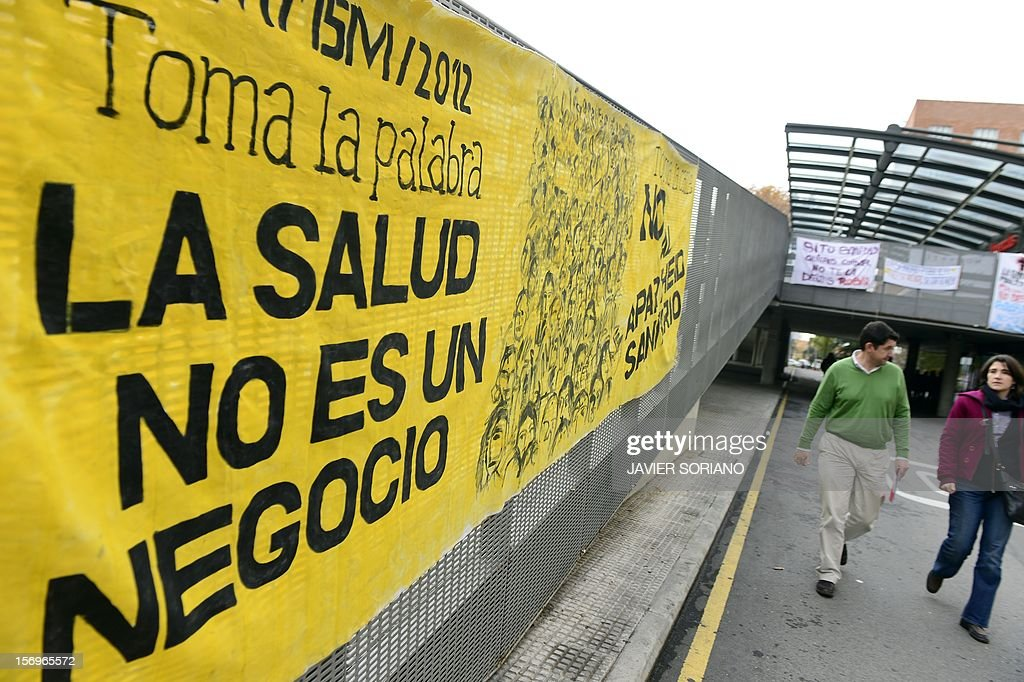 People walk past a banner reading 'Health is not a business' outside the Hospital Clinico San Carlos in Madrid on November 26, 2012. Spanish doctors, nurses and hospital staff denounce budget cuts and privatisations. The health sector has been hard hit by the austerity policies implemented by the rightwing government of Mariano Rajoy, which is trying to cut the public deficit in the eurozone's fourth largest economy.