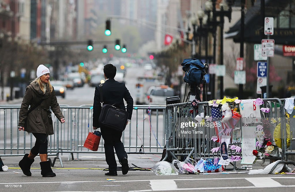 People walk past a barricade and makeshift memorial blocking a still closed section of Boylston Street near the site of the Boston Marathon bombings on April 23, 2013 in Boston, Massachusetts. Business owners and residents of the closed section were allowed to return to their properties today while under escort of city staff.
