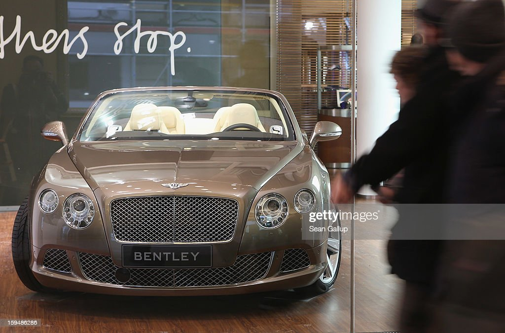 People walk past a Bentley convertible car on display at a Volkswagen Group showroom on January 14, 2013 in Berlin, Germany. Volkswagen Group, which includes the VW, Audi, Porsche, Skoda, SEAT, Bentley and Bugatti brands, delivered a record 9.07 million cars to customers in 2012. Rising sales in the Americas and Asia helped to offset a drop in sales in western Europe.